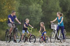Young happy mother, father and two cute blond children, boy and girl riding bicycles on pebbled river bank on blurred bright summe stock photo