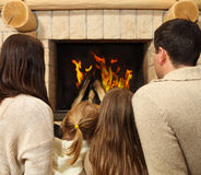 Young happy mother, father and two daughters by a fireplace Royalty Free Stock Photography