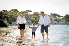 Young happy mother and father walking on beach in family vacation concept Stock Image