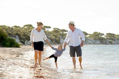 Young happy mother and father walking with little daughter on beach in family vacation concept Stock Photos