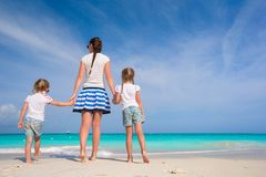 Young happy mother and her adorable daughters having fun at exotic beach on sunny day Royalty Free Stock Image