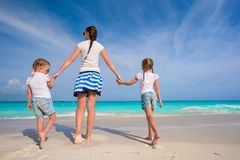 Young happy mother and her adorable daughters having fun at exotic beach on sunny day Stock Photography