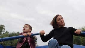 Young happy mother and her little son spending time together in park with lake. Lovely mom and son having fun outside. Young mothe. R sails on boat with son stock footage
