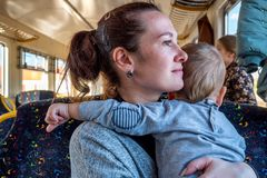 Young happy mother holding baby while he pulls her hair while travelling by train.  stock images