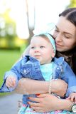 Young happy mother holding little daughter wearing jeans jacket. stock photo