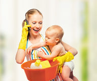 Young happy mother is a housewife with a baby does homework and Stock Photo