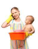 Young happy mother is a housewife with a baby does homework and Royalty Free Stock Photos