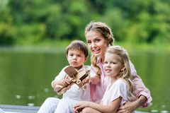young happy mother and kids riding boat on lake royalty free stock images
