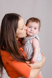 Young happy mother kissing her daughter. Portrait of mother and baby at the hands of six mothers stock photo