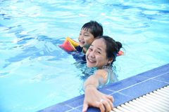 Young happy mother and little son in a swimming pool royalty free stock image