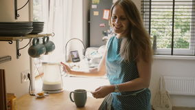 Young happy mother pouring hot water in the mug to make a cup of tea. Slow mo, Steadicam shot stock video footage
