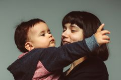 Close up portrait of mother and son. Young happy mother with short dark hair with her son toddler pointing somewhere, wearing hoodie Royalty Free Stock Photo