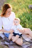 Young happy mother sitting with little child on plaid, grass on background. royalty free stock photography