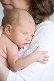 Young happy mother tenderly hugging her newborn baby royalty free stock images