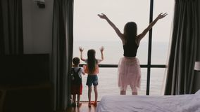 Young happy mother with two little kids together jumping and having fun at large window with epic sea view slow motion. stock video