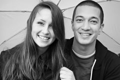 Young happy multi-racial attractive couple. Young happy smiling multi-racial attractive couple holding an umbrella black and white stock image