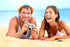 Young happy multicultural couple on beach. Having fun laughing during summer holiday vacation. Caucasian hipster men with retro vintage camera and asian women Royalty Free Stock Images