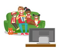 Multicultural family watching football match on TV. Young happy multicultural family sitting on sofa, eating popcorn and watching football game together on Stock Image