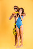 Young happy multiracial couple having fun playing with water guns Royalty Free Stock Images