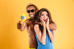 Young happy multiracial couple having fun playing with water guns Stock Image