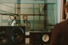 young happy musicians recording song behind glass at studio and showing stock photo