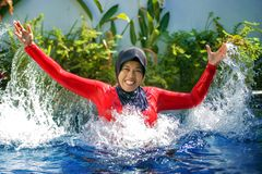 Young happy muslim woman playing with water excited in resort swimming pool splashing and having fun wearing traditional islam. Young happy and cheerful muslim stock images