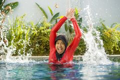 Young happy muslim woman playing with water excited in resort swimming pool splashing and having fun wearing traditional islam. Young happy and cheerful muslim royalty free stock image