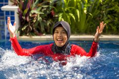 Young happy muslim woman playing with water excited in resort swimming pool splashing and having fun wearing traditional islam. Young happy and cheerful muslim royalty free stock images