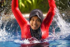 Young happy muslim woman playing with water excited in resort swimming pool splashing and having fun wearing traditional islam. Young happy and cheerful muslim stock photo
