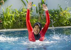 Young happy muslim woman playing with water excited in resort swimming pool splashing and having fun wearing traditional islam. Young happy and cheerful muslim stock photography