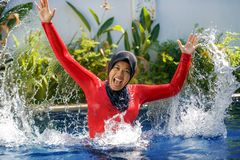 Young happy muslim woman playing with water excited in resort swimming pool splashing and having fun wearing traditional islam. Young happy and cheerful muslim stock image