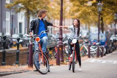 Young happy caucasian couple on bikes in old streets in Amsterdam. Young happy ouple on bikes in old streets in Amsterdam Royalty Free Stock Image