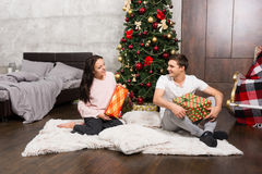 Young happy pair in pajamas rejoice at their presents while sitt Royalty Free Stock Photography