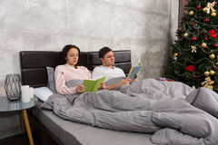 Young happy pair reading books while lying in the bed in the bed Stock Images