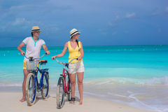 Young happy pair riding bikes on white tropical beach Stock Images