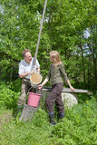 Young happy pair at a well,pours water in a bucket royalty free stock photography
