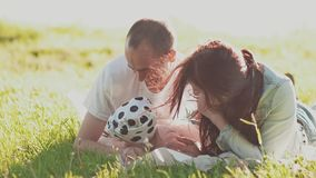Young happy parents and a little cute daughter are lying in the green grass in the bright rays of the summer sun. Kiss stock video