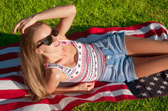 Young happy patriot woman holding the United States flag Royalty Free Stock Photo