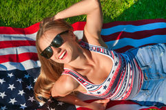 Young happy patriot woman on the united states flag Royalty Free Stock Image