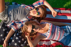 Young happy patriot women on the united states flag Royalty Free Stock Photo