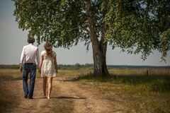 Young happy people or a couple holding hands walking along the path in the Park, against a large beautiful spreading tree. Lovers stock photos