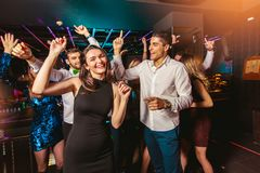 Happy people are dancing in club. Nightlife and disco concept royalty free stock image