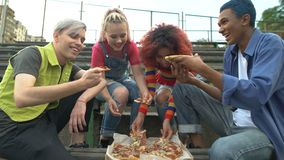 Young happy people eating pizza outdoors, friends relaxing together outdoors