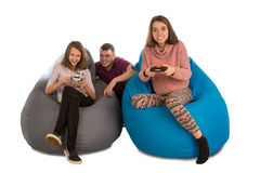 Young happy people are enthusiastic about playing video games while sitting on blue and grey beanbag chairs isolated on white royalty free stock image