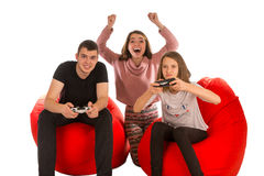 Young happy people are enthusiastic about playing video games wh. Ile sitting on red beanbag chairs isolated on white background Royalty Free Stock Photos