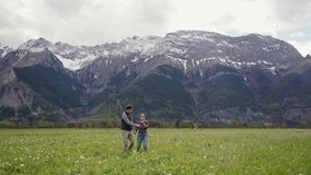 Young happy people holding hands running on dandelion field In mountains. Front view. General plan. 4k stock footage