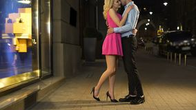 Young and happy people lovely embracing, standing in brightly illuminated street. Stock footage stock video footage