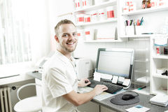 Young happy pharmacist sitting. And working on the computer in lab. Checking the proper preparation medicine. Color toned image Royalty Free Stock Photo