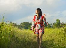 Young happy and playful Asian Chinese woman in beautiful dress having fun enjoying holidays excursion on grass tropical field smil. Ing cheerful in tropical Royalty Free Stock Images