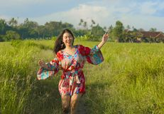 Young happy and playful Asian Chinese woman in beautiful dress having fun enjoying holidays excursion on grass tropical field smil. Ing cheerful in tropical stock photography